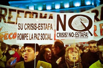 Des manifestants lors d'une manifestation contre une réforme du travail qui vise notamment à faciliter les licenciements, à réduire le salaire minimum et à réduire les droits au chômage. Sur une des pancartes que les manifestants portent on peut lire : « Une crise ? Non, une escroquerie ! ».